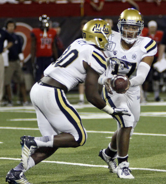 UCLA's starting quarterback Brett Hundley (17) hands off the ball to Myles Jack (30) in the second half of an NCAA college football game against Arizona, Saturday, Nov. 9, 2013 in Tucson, Ariz. UCLA won 31 - 26. (AP Photo/Wily Low)