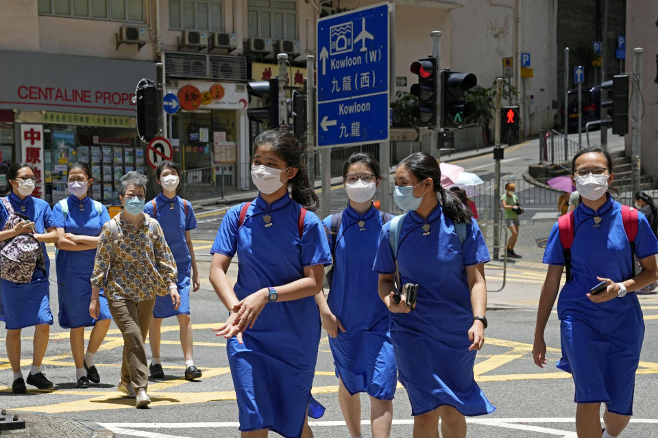 Students wearing face masks to prevent the spread of the coronavirus, walk across a street in Hong Kong, Thursday, June 10, 2021. Government officials said Thursday that they will expand the vaccination drive to about 240,000 children from 12 to 15 years old starting Friday, joining other countries such as Singapore and the U.S. that have started vaccinating children. (AP Photo/Kin Cheung)