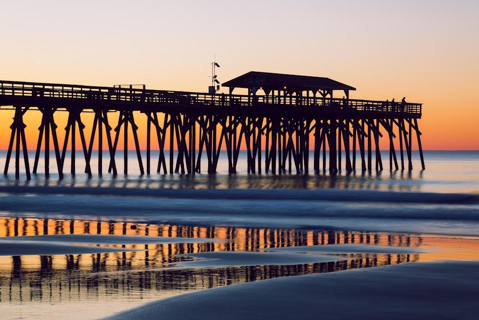The silhouette of the Myrtle Beach State Park Pier and fisherman during an early morning sunrise on the Atlantic Ocean. (Getty)
