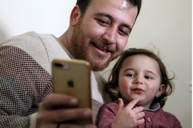 Syrian father Abdullah Mohammed checks a phone with his three-year-old daughter Salwa at their home in Sarmada, a town in Syria's last rebel pocket in the Idlib province, 19 February
