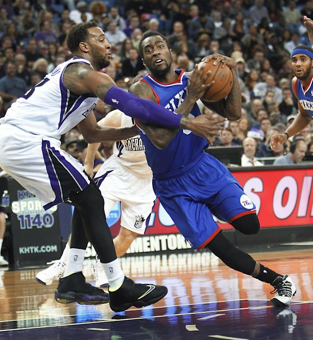 Philadelphia 76ers guard Tony Wroten, right, drives to the basket against Sacramento Kings defender Derrick Williams during the first half of an NBA basketball game in Sacramento, Calif., on Thursday, Jan. 2, 2014. (AP Photo/Steve Yeater)