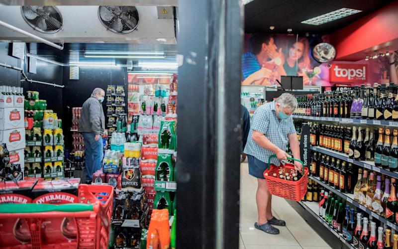 Man fills shopping basket in off licence - AFP