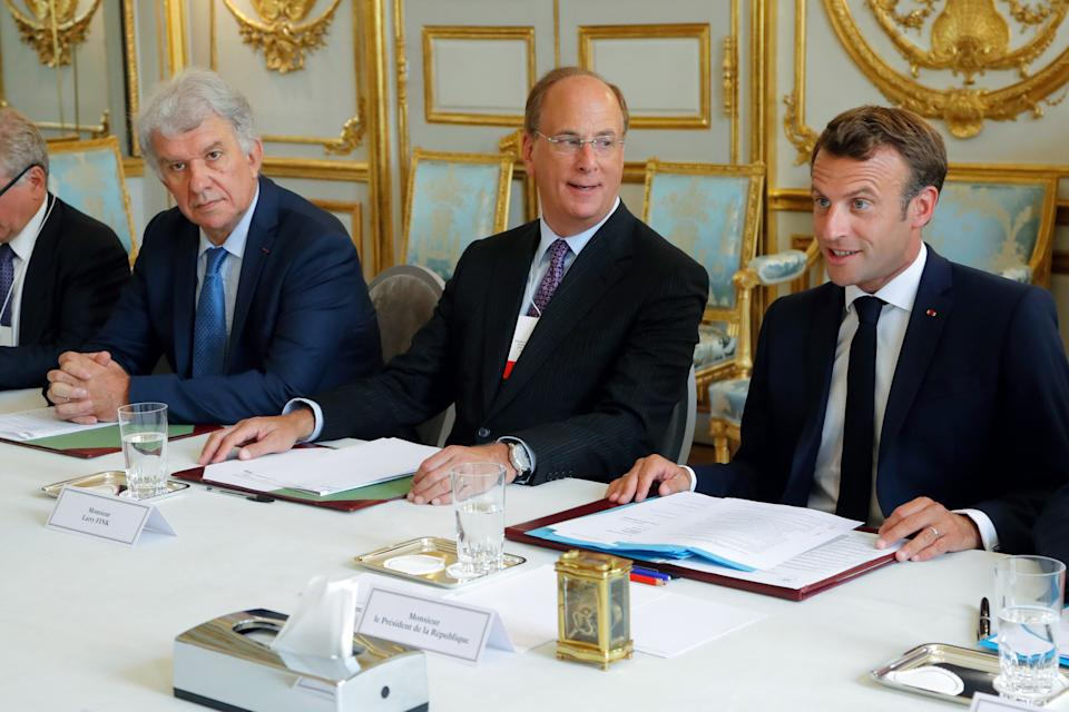 Amundi CEO Yves Perrier (L), chairman and CEO of BlackRock, Larry Fink (C) sit alongside French President Emmanuel Macron as they attend a meeting between the French President and representatives of investment funds and sovereign wealth funds to fight climate change at the Elysee Palace in Paris on July 10, 2019. (Photo by Michel Euler / POOL / AFP)        (Photo credit should read MICHEL EULER/AFP via Getty Images)