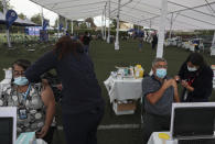 Healthcare workers inject people with the Sinovac COVID-19 vaccine at La Pintana Sports Complex turned into a makeshift vaccination site, in Santiago, Chile, Thursday, March 11, 2021, on the one-year anniversary that the World Health Organization declared the coronavirus a pandemic. (AP Photo/Esteban Felix)