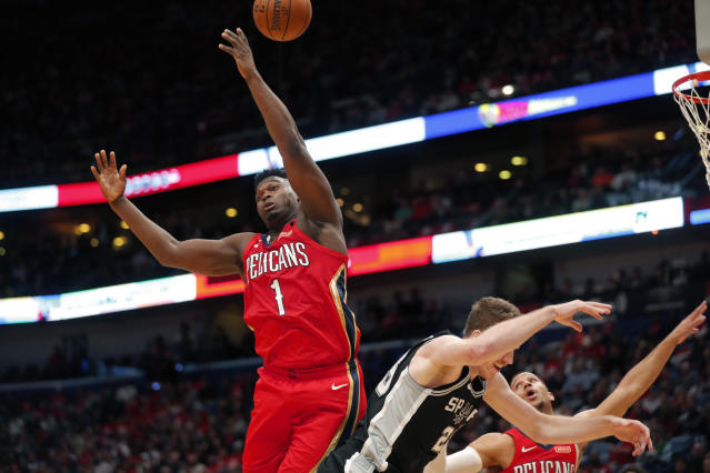 New Orleans Pelicans forward Zion Williamson (1) battles for a rebound against San Antonio Spurs center Jakob Poeltl in the second half of an NBA basketball game in New Orleans, Wednesday, Jan. 22, 2020. The Spurs won 121-117. (AP Photo/Gerald Herbert)