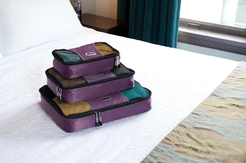 This undated image provided by eBags.com shows a set of the company's packing cubes on a bed in a hotel room. Peter Cobb, the company's co-founder, says the packing cubes _ which help travelers organize their belongings and save space when packing for trips _ are the website's #1 bestselling product out of 50,000. (AP Photo/eBags.com)