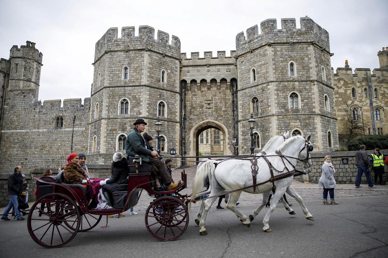 Tourists ride in a horse-drawn carriage past the main entrance of Windsor Castle in Windsor, west of London