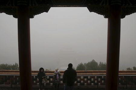 The Forbidden City is barely seen from the top of Jingshan Park as visitors take pictures on an extremely polluted day as hazardous, choking smog continues to blanket Beijing, China December 1, 2015. REUTERS/Damir Sagolj