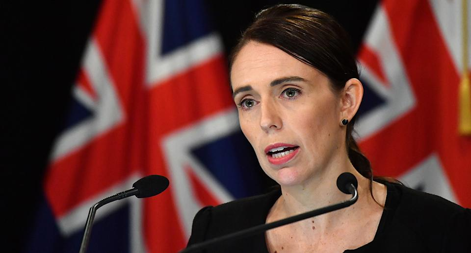 NZ Prime Minister Jacinda Ardern speaking in Parliament with two microphones in front of her.