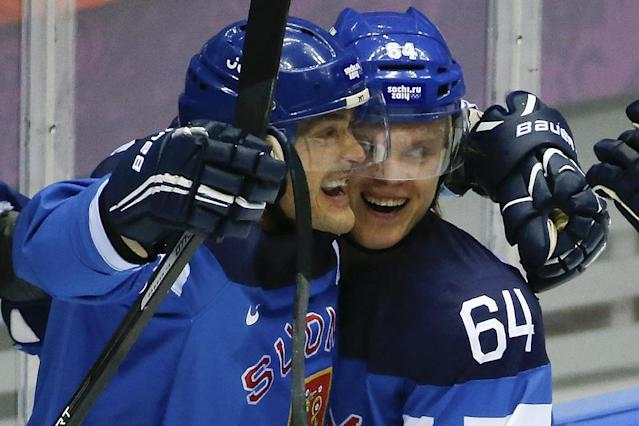 Finland forward Teemu Selanne and Finland forward Mikael Grandlund celebrate a second period goal against Russia during a men's quarterfinal ice hockey game at the 2014 Winter Olympics, Wednesday, Feb. 19, 2014, in Sochi, Russia