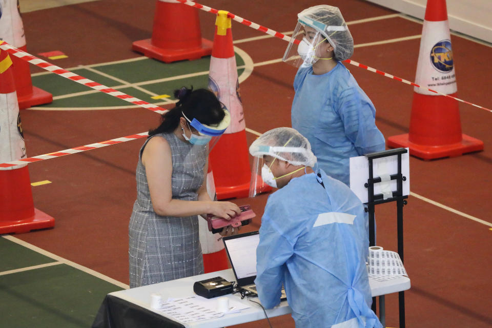 Healthcare workers dressed in personal protective equipment attend to a resident during registration for a mandatory swab test at a temporarily COVID-19 testing centre on June 20, 2021 in Singapore. The authorities have set up special testing operations to contain the potential community transmission after several clusters outbreak at a market and food centre. According to the local media, the Ministry of Health has detected 428 local COVID-19 cases of the B16172 (Delta) variant as of May 31, which is more transmissible, virulent or resistant to public health measures. (Photo by Suhaimi Abdullah/NurPhoto via Getty Images)