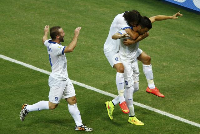 Greece's Samaris celebrates with teammates scoring against Ivory Coast during their 2014 World Cup Group C soccer match at the Castelao arena in Fortaleza