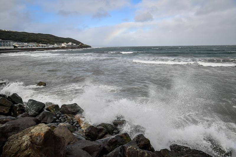 A rainbow forms in the distance as waves hit boulders on the shoreline at Westward Ho! in Devon, as winds of up to 70mph are expected along the coast during the next 36 hours along with up to 90mm of rain as Storm Francis hit the UK. (Photo by Ben Birchall/PA Images via Getty Images)