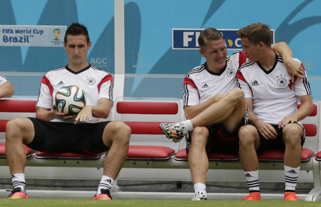 Germany's Miroslav Klose, left, holds a soccer ball while Bastian Schweinsteiger, center, talks to Erik Durm during a training session in Recife, Brazil, Wednesday, June 25, 2014. Germany will play the United States in group G of the 2014 soccer World Cup on June 26. (AP Photo/Julio Cortez)