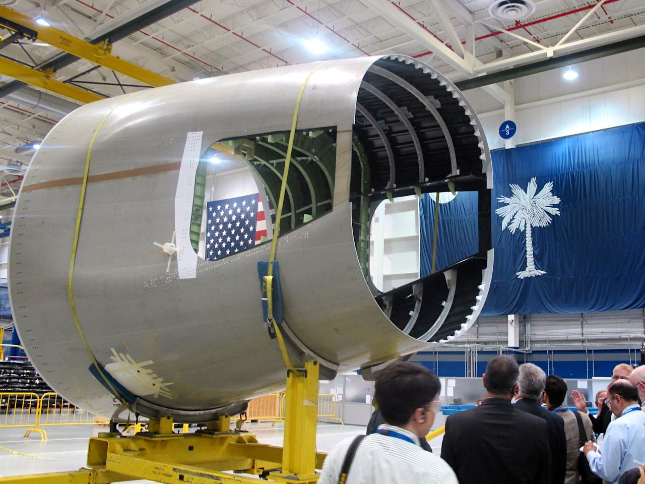 Reporters tour the aft body assembly plant at Boeing's $750 million plant in North Charleston, S.C., on Friday, April 27, 2012. The company was rolling out the first of its new 787s manufactured at its South Carolina plant which opened in 2011. (AP Photo/Bruce Smith).