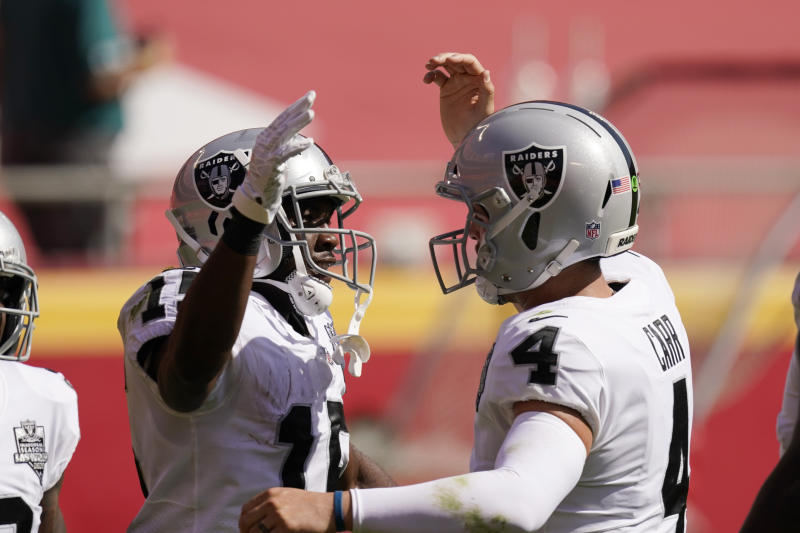 Raiders wide receiver Nelson Agholor, left, celebrates with quarterback Derek Carr after catching a 59-yard touchdown pass in their win over the Chiefs on Sunday. (AP Photo/Charlie Riedel)