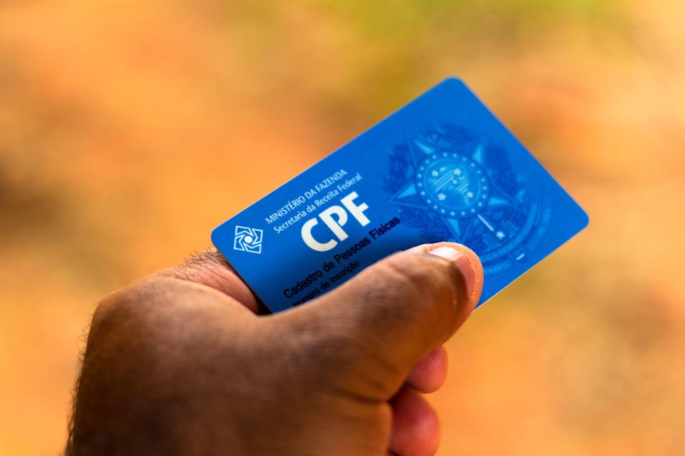 """BRAZIL - 2019/08/28: A man displays his document """"Cadastro de Pessoa Física"""" (CPF). The document guarantees authenticity and integrity in the electronic communication between people in Brazil. (Photo Illustration by Rafael Henrique/SOPA Images/LightRocket via Getty Images)"""