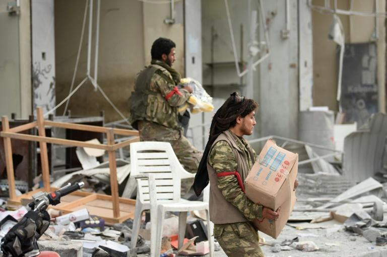 Turkish-backed Syrian fighters loot shops after seizing control of the northwestern Syrian city of Afrin from the Kurdish People's Protection Units (YPG) on March 18, 2018