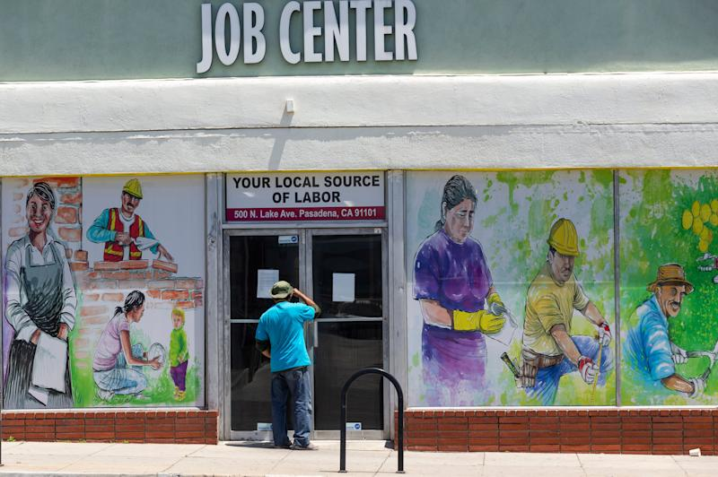 A worker looks inside the closed doors of the Pasadena Community Job Center in Pasadena, Calif., May 7, 2020, during the coronavirus outbreak. The center normally connects members of the community, residential customers and small business owners with skilled day laborers.