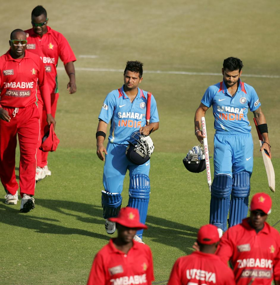 India's captain Virat Kohli (R) and Suresh Raina (C) walk off the pitch after their victory during the 3rd match of the 5 cricket ODI series between Zimbabwe and India at Harare Sports Club on July 28, 2013. AFP PHOTO / JEKESAI NJIKIZANA        (Photo credit should read JEKESAI NJIKIZANA/AFP/Getty Images)