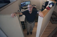 John Gold, self-employed graphics designer, poses in his shared office cubical in Portland, Maine, Wednesday, Oct. 23, 2019. Gold has been covered by the Affordable Care Act since it started, and plans on signing up again when the enrollment season starts Nov. 1. The 2020 sign-up season for the Affordable Care Act is getting underway with premiums down slightly in many states and more health plan choices for consumers. (AP Photo/Charles Krupa)