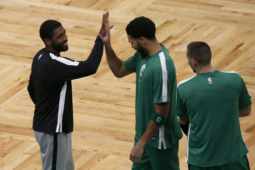 Brooklyn Nets guard Kyrie Irving, left, smiles as he greets former teammate Boston Celtics forward Jayson Tatum (0) as Celtics' Daniel Theis, right, looks on before an NBA preseason basketball game, Friday, Dec. 18, 2020, in Boston. (AP Photo/Mary Schwalm)