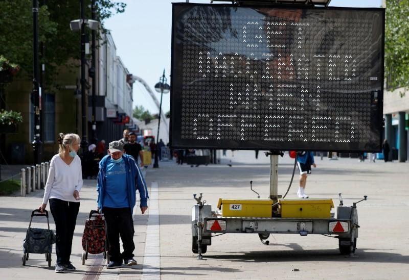 People pull shopping carts as they walk past an information board, amid the COVID-19 outbreak, in Bolton