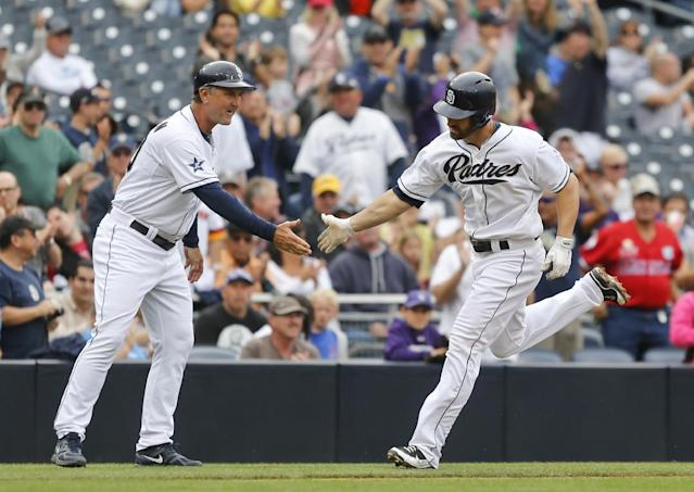 San Diego Padres' Xavier Nady is congratulated by third base coach Glenn Hoffman while rounding the bases on a solo home run against the Colorado Rockies during the fourth inning of a baseball game Thursday, April 17, 2014, in San Diego. (AP Photo/Lenny Ignelzi)
