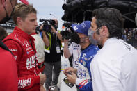 Marcus Ericsson, left, of Sweden, talks with Tony Kanaan, second from right, of Brazil, and Dario Franchitti, right, during qualifications for the Indianapolis 500 auto race at Indianapolis Motor Speedway, Saturday, May 22, 2021, in Indianapolis. (AP Photo/Darron Cummings)