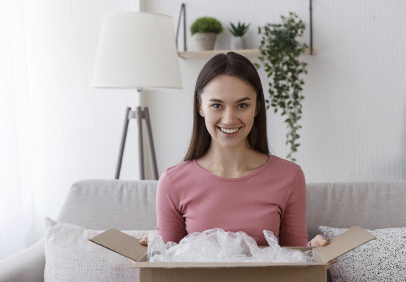 Smiling young woman unboxing international parcel at home, delivery concept