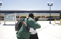 In this photo taken Wednesday, July 17, 2013, Ida Johnson greets her son, Ronnie Greene, at the Amtrak stop in Madera, Calif. Johnson, moved to the Central Valley after she retired from a job in the San Francisco Bay Area, and takes the train to visit friends who still live there, looks forward to the construction of a high-speed rail system.The state's plan to build the first high-speed rail system in the nation is intended to alleviate gridlock, connect the Central Valley to better jobs, and ease pollution, but many residents oppose the $68 billion project.(AP Photo/Rich Pedroncelli)