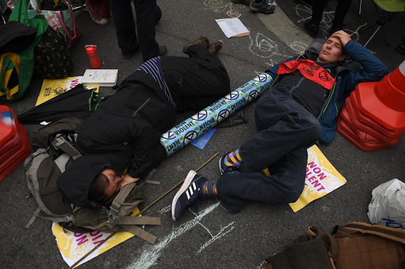 LONDON, ENGLAND - OCTOBER 07: Extinction Rebellion protesters who are attached by a concrete tube lie down at Whitehall on October 7, 2019 in London, England. Climate change activists are gathering to block access to various government departments as they start a two week protest in central London (Photo by Chris J Ratcliffe/Getty Images)