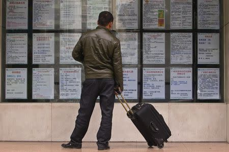 A man with a suitcase looks at recruitment advertisements outside a labour market in Guangzhou