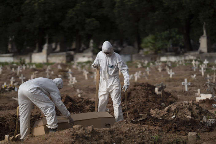 """Cemetery workers in protective clothing maneuver the coffin of 57-year-old Paulo Jose da Silva, who died from the new coronavirus, in Rio de Janeiro, Brazil, Friday, June 5, 2020. According to Monique dos Santos, her stepfather mocked the existence of the virus, didn't use a mask, didn't take care of himself, and wanted to shake hands with everybody. """"He didn't believe in it and unfortunately he met this end. It's very sad, but that's the truth,"""" she said. (AP Photo/Leo Correa)"""