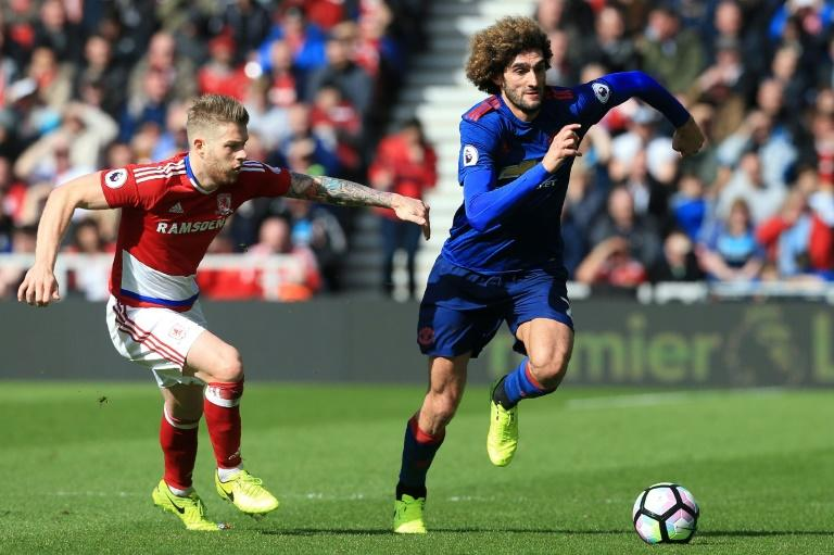 Middlesbrough's midfielder Adam Clayton vies with Manchester United's Marouane Fellaini (right) during their English Premier League match at Riverside Stadium in Middlesbrough on March 19, 2017
