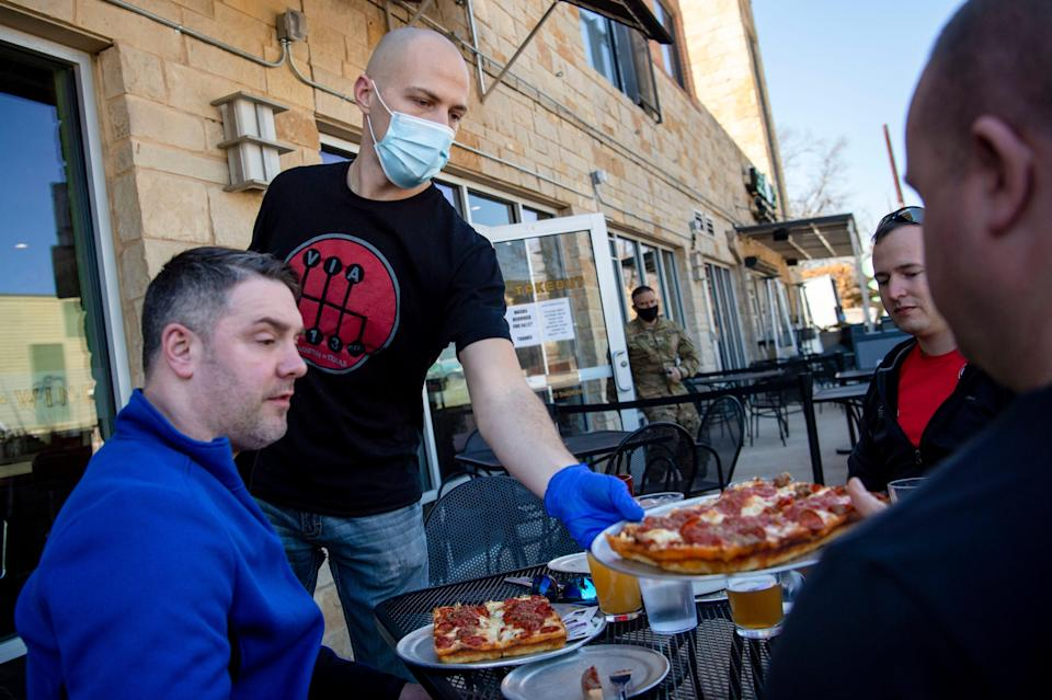 Server Jared Smith gives Sam Webster of New York his pizza order at Via 313 Pizza on March 3 in Austin, Texas. Businesses will be able to operate at full capacity beginning March 10.