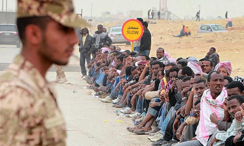 A Saudi police officer stands next to undocumented foreign workers in Riyadh, Saudi Arabia.