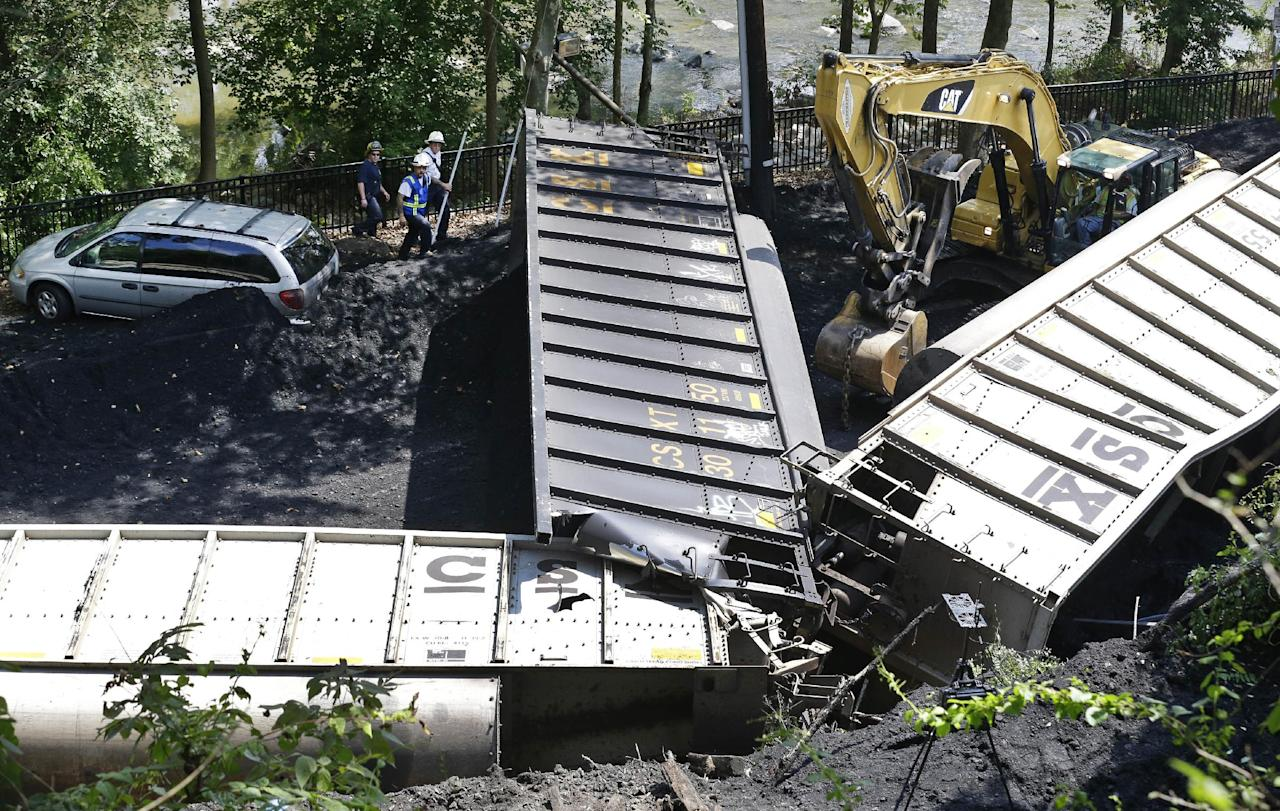 Officials, top left, inspect part of a CSX freight train that derailed alongside a parking lot overnight in Ellicott City, Md., Tuesday, Aug. 21, 2012. Authorities say the train, hauling coal from West Virginia to Maryland, derailed and fell from a bridge near Baltimore, killing two college students who were on the tracks. Howard County officials say 21 of the train's 80 cars flipped over around midnight Monday. (AP Photo/Patrick Semansky)