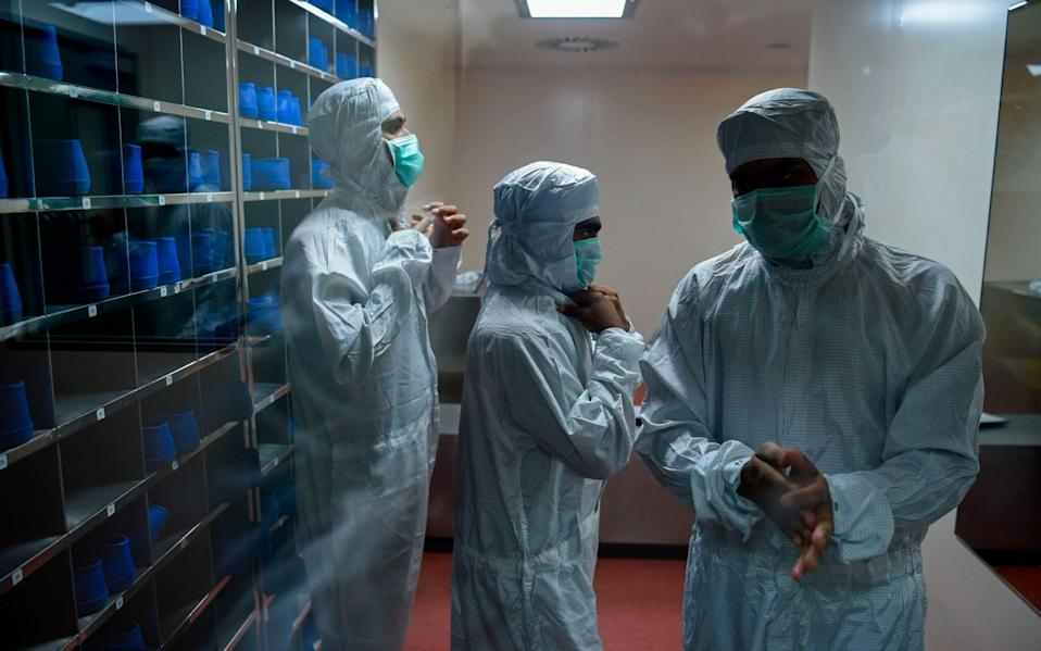 Employees prepare themselves before getting inside a lab where Covishield, AstraZeneca-Oxford's coronavirus vaccine is being manufactured, at India's Serum Institute - PUNIT PARANJPE/AFP via Getty Images
