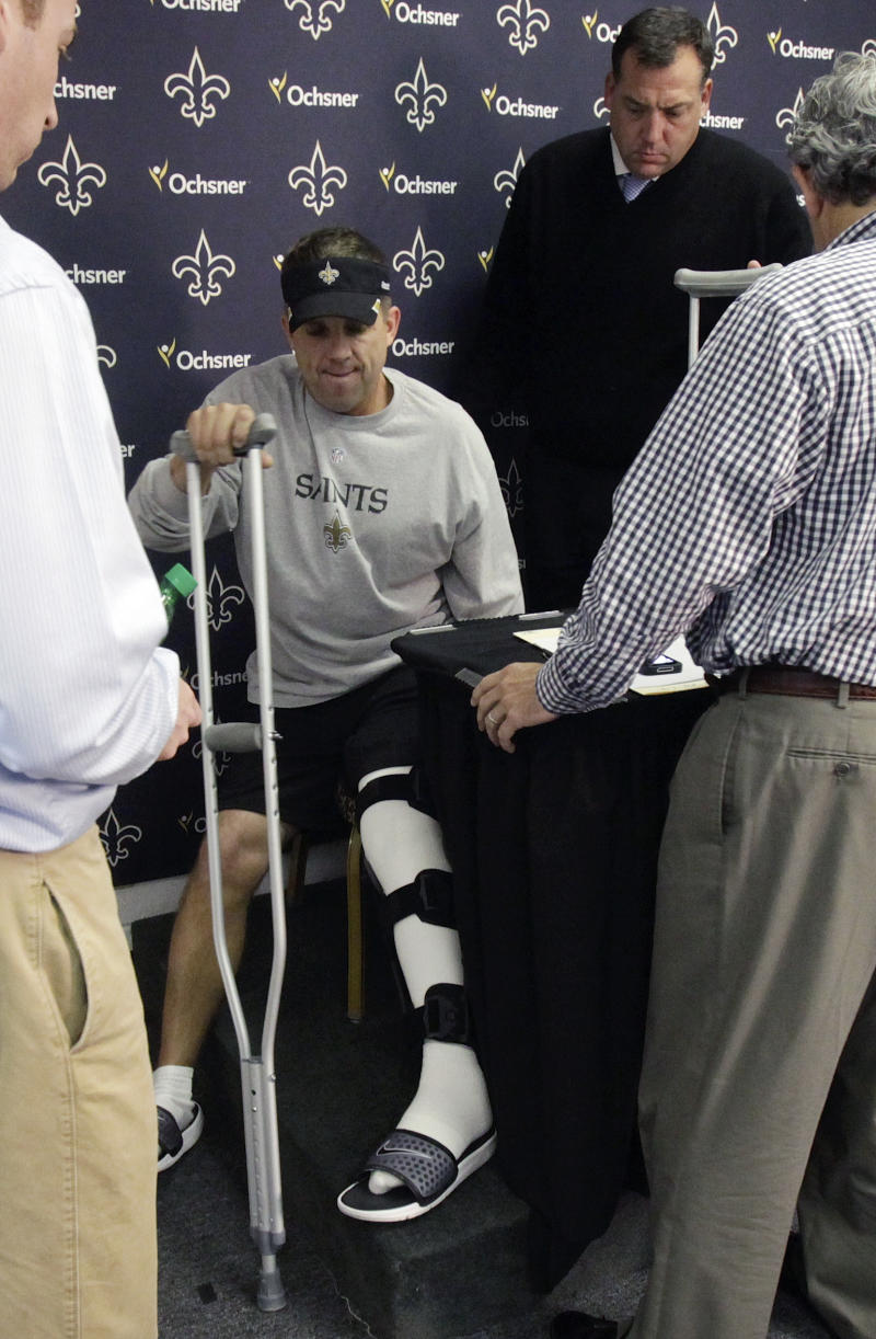 New Orleans Saints coach Sean Payton uses a crutch to get up as he leaves a news conference at the NFL football team's training facility in Metairie, La., Thursday, Oct.  20, 2011. This Payton's first event since breaking his left leg on the sidelines during a game against the Tampa Bay Buccaneers last Sunday. (AP Photo/Bill Haber)