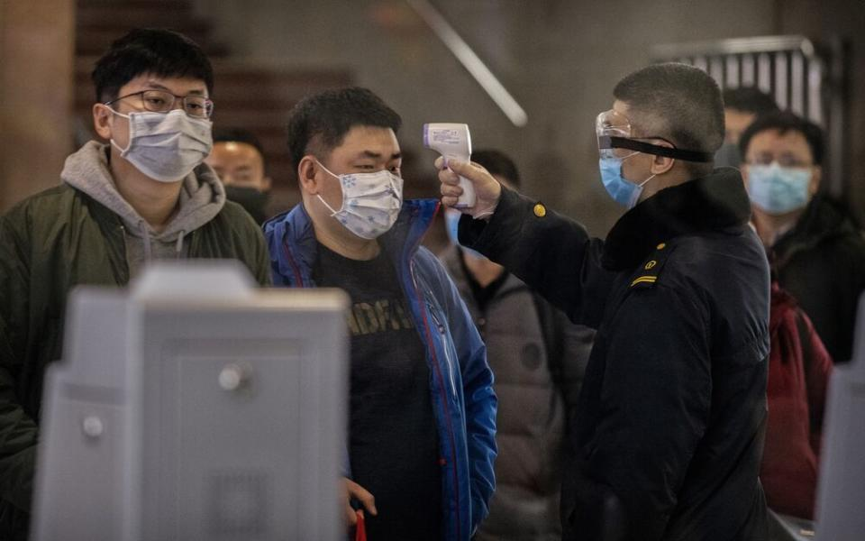 A Chinese passenger that just arrived on the last bullet train from Wuhan to Beijing is checked for a fever by a health worker at a Beijing railway station. | Kevin Frayer/Getty Images