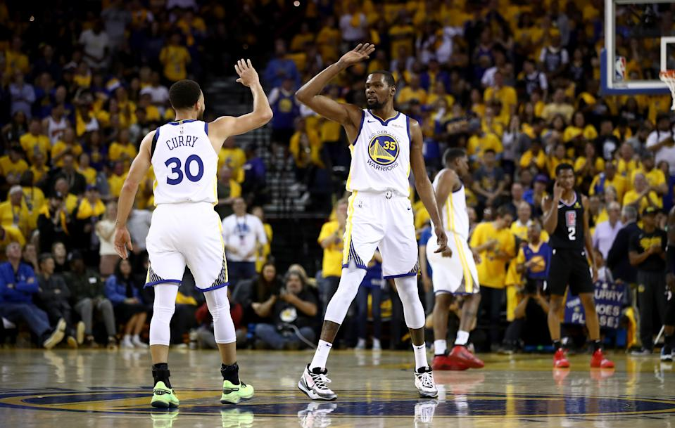 OAKLAND, CALIFORNIA - APRIL 13:  Stephen Curry #30 high fives Kevin Durant #35 of the Golden State Warriors during their game against the LA Clippers during Game One of the first round of the 2019 NBA Western Conference Playoffs at ORACLE Arena on April 13, 2019 in Oakland, California. NOTE TO USER: User expressly acknowledges and agrees that, by downloading and or using this photograph, User is consenting to the terms and conditions of the Getty Images License Agreement. (Photo by Ezra Shaw/Getty Images)