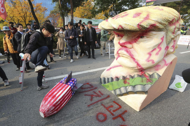 """<p>A protester tramples a mock U.S. missile during a rally to oppose the visit by U.S. President Donald Trump in front of the National Assembly in Seoul, South Korea, Nov. 8, 2017. The words on the ground read """"Maniac."""" (Photo: Ahn Young-joon/AP) </p>"""