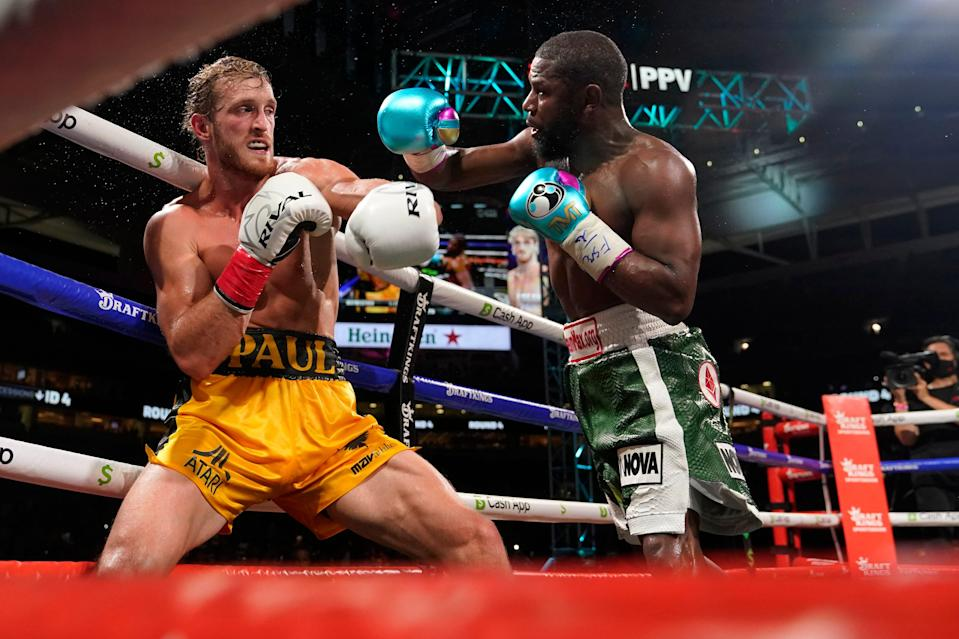 Floyd Mayweather throws a punch at Logan Paul during a boxing match at Hard Rock Stadium in Miami Gardens, Fla.