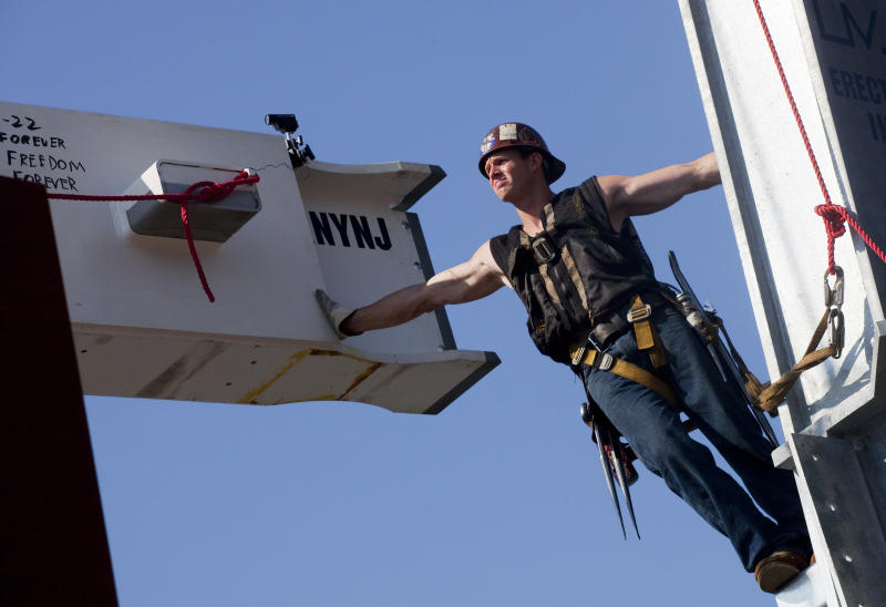 """Ironworker Billy Geoghan reaches out to maneuver a steel beam as it is lifted by crane to the 104th floor of 1 World Trade Center, Thursday, Aug. 2, 2012 in New York. The beam was signed by President Barack Obama with the notes: """"We remember,"""" ''We rebuild"""" and """"We come back stronger!"""" during a ceremony at the construction site June 14. Since then the beam has been adorned with the autographs of workers and police officers at the site. The beam will be sealed into the structure of the tower, which is scheduled for completion in 2014. (AP Photo/Mark Lennihan)"""
