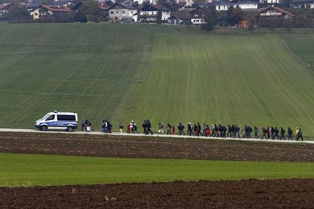 FILE PHOTO: Immigrants are escorted by German police to a registration centre, after crossing the Austrian-German border in Wegscheid near Passau, Germany, October 20, 2015. REUTERS/Michael Dalder/File Photo