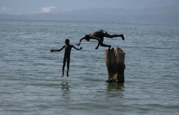 In this Sept. 6, 2012 photo, youths jump into Lake Azuei in Thomazeau, Haiti, near the border with the Dominican Republic. The waters' rise has worsened exponentially in recent years, especially after heavy rains in 2007 and 2008 hit the island of Hispaniola. Tropical Storm Isaac dumped more water on the region last month, sparking more damage. (AP Photo/Dieu Nalio Chery)