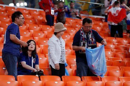 Soccer Football - World Cup - Group H - Japan vs Senegal - Ekaterinburg Arena, Yekaterinburg, Russia - June 24, 2018 Japan fans clean up after themselves after the match REUTERS/Andrew Couldridge