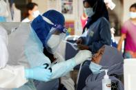 FILE PHOTO: A medical worker collects a swab sample from a Top Glove worker to be tested for the coronavirus disease (COVID-19) outside a hostel under enhanced lockdown in Klang
