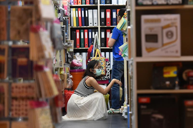 A woman wears a face mask inside a shop as a preventive measure against COVID-19 in Singapore on 20 March, 2020. (PHOTO: AFP via Getty Images)
